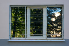 Fenêtre en plastique sale sur le mur d'un bâtiment avec un gril en métal Images stock