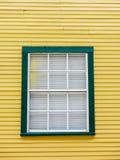 Fenêtre encadrée par vert sur un bâtiment jaune Photo stock