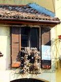 Fenêtre ensoleillée d'une vieille maison, avec les fleurs sèches et les volets presque en baisse-à part image libre de droits