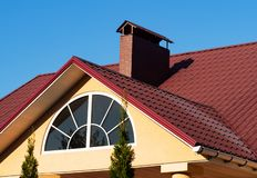 Fenêtre et cheminée arquées de brique sur le toit de tuile rouge en métal sous le ciel bleu, extérieur de maison photographie stock libre de droits