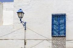 Fenêtre et lampe bleues sur la maison en Tunisie Photo libre de droits