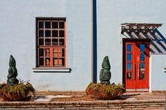 Fenêtre et porte rouges sur un mur bleu photo stock