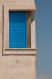 Fenêtre faisante le coin avec les volets bleus Images libres de droits