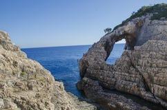 Fen?tre naturelle dans la pierre dans Korakonissi et les gens sautant dans l'eau d'une falaise photographie stock libre de droits