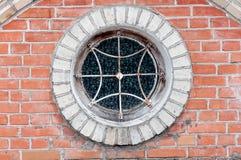 Fenêtre ronde avec le gril sur le mur de briques Photos libres de droits