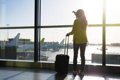 Fenêtre se tenante prêt de femme dans l'aéroport Photos stock