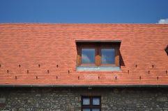 Fenêtre sur la tuile avec le fond de ciel bleu Image stock