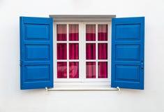 Fenêtre sur le mur blanc avec les abat-jour bleus du soleil Images stock