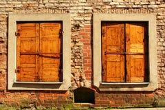 Fenêtres à volets fermées avec des abat-jour dans le mur de briques rouge Image libre de droits