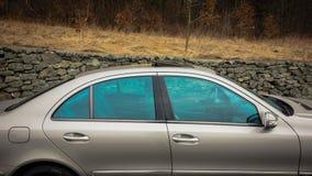 Fenêtres électriques d'isolement par bleu, toit ouvrant ouvert, vue de côté droit, voiture de luxe allemande en or métallique Photo stock