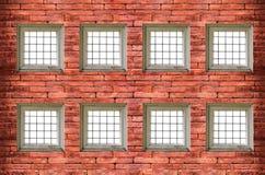 fenêtres avec des barres de fer sur le vieux mur de briques rouge Images libres de droits