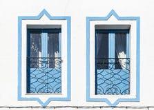 Fenêtres bleues sur un mur blanc Photographie stock libre de droits