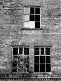 Fenêtres cassées dans un immeuble de brique abandonné abandonné Images libres de droits