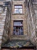 Fenêtres cassées dans un vieux bâtiment saccagé abandonné vide Image stock