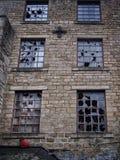 Fenêtres cassées dans un vieux buildi en pierre saccagé abandonné vide Image libre de droits