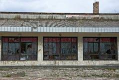 Fenêtres cassées derrière des barres sur le mur d'un bâtiment abandonné sur la rue Photo libre de droits