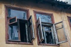 Fenêtres cassées ouvertes de brûler par la maison du feu Images libres de droits