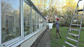 Fenêtres cultivées en serre de nettoyage de fille avec de la pression de jet d'eau banque de vidéos