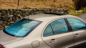 Fenêtres d'isolement/teintées de bleu et toit ouvert du soleil - voiture allemande de berline en or métallique Images stock