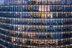 Fenêtres de bureau de gratte-ciel et employé de bureau par nuit photos libres de droits