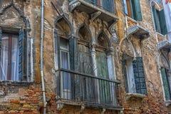 Fenêtres de cru dans le mur d'une maison de brique au-dessus du canal photo stock