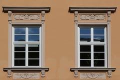 Fenêtres de vintage décorées des ornements riches sur le mur orange dans la rue de Maximillian, Augsbourg, Allemagne photos stock