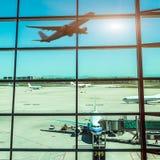 Fenêtres et avion d'aéroport au coucher du soleil Image stock