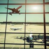 Fenêtres et avion d'aéroport au coucher du soleil Photos stock