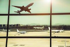 Fenêtres et avion d'aéroport au coucher du soleil Photo libre de droits