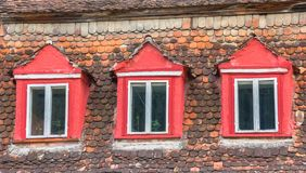 Fenêtres et tuiles de toit colorées sur une maison dans Sighisoara Image stock
