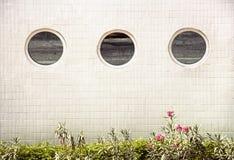 3 fenêtres rondes de miroir dans une rangée sur un bâtiment carrelé blanc Photo libre de droits