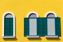 Fenêtres vertes sur la fenêtre jaune de mur chez le Venezia Photo stock
