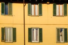Fenêtres vertes sur un mur jaune au coucher du soleil Photos libres de droits
