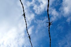 Fence. Barbed wire on clouds Stock Photos