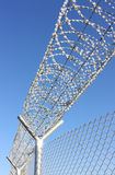Fence. Security chain link fence with razor/concertina wire and barb wire on top isolated on a blue sky background Stock Photos