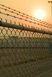 Fence. Chain link fence with an eerie feeling cast by hazy light from the sun threw an extremely smokey day royalty free stock photos