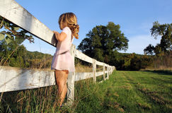 Fence. Little girl looking over a white fence Stock Photography