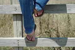 On the Fence. Partial shot of girl sitting on fence wearing jeans and yellow flip-flops Royalty Free Stock Image