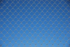 Fence. Blue background with wire fence in front stock photography