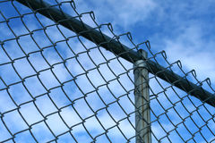 Fence. A chain-link fence in front of a bright blue sky Royalty Free Stock Image
