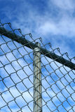 Fence. A chain-link fence in front of a bright blue sky Stock Photography