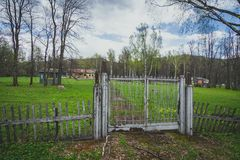 Fence before abandoned territory. On the territory there are old abandoned and partially crushed buildings Royalty Free Stock Photo