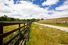 Fence Along a Country Road. Wooden fence parallels a narrow country road in rural central California Stock Image