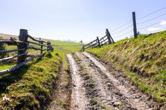 Fence along the country road through hillside. Lovely rural scenery stock image