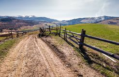 Fence along the country road in rural area. Lovely agricultural landscape in Carpathian mountains. grassy fields on hill in springtime. Location Volovets Stock Photos