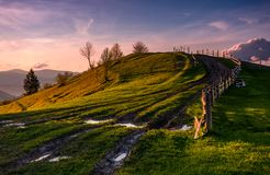 Fence along the country road uphill at dusk. Wooden fence along the country dirt road uphill the grassy knoll in springtime at dusk. Spectacular nature scenery Royalty Free Stock Photography