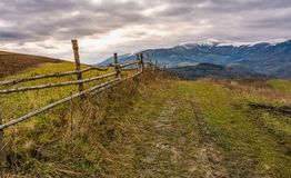 Fence along dirt road in mountainous rural area. Agricultural fields on hills in late autumn. mountain ridge with snowy tops in the distance Royalty Free Stock Image