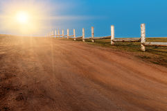 Fence along the gravel road. With sunlight Stock Photo