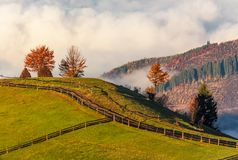 Fence along the path in foggy mountains. Gorgeous sunrise in autumnal rural scenery Stock Image