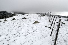 Fence along a snowed wide mountain ridge under dark clouds Stock Photos